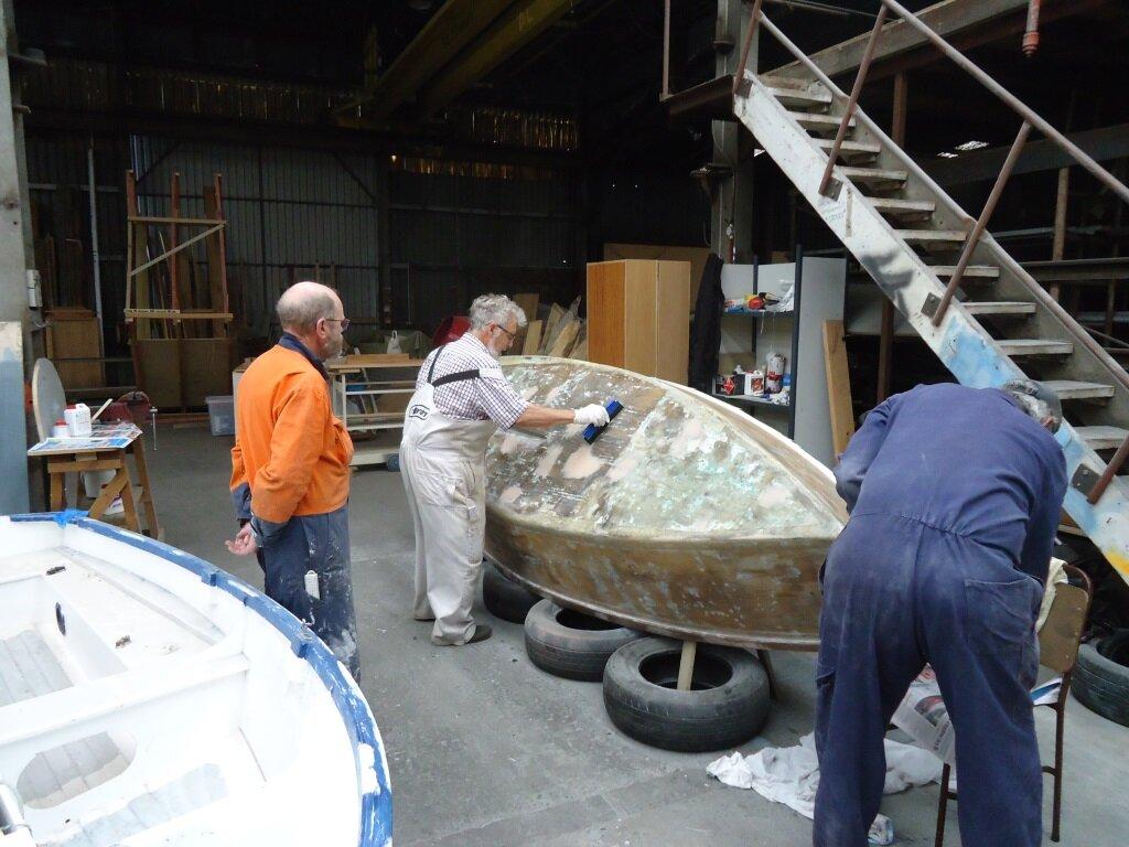 Gavin helps Ron fiberglass boat.