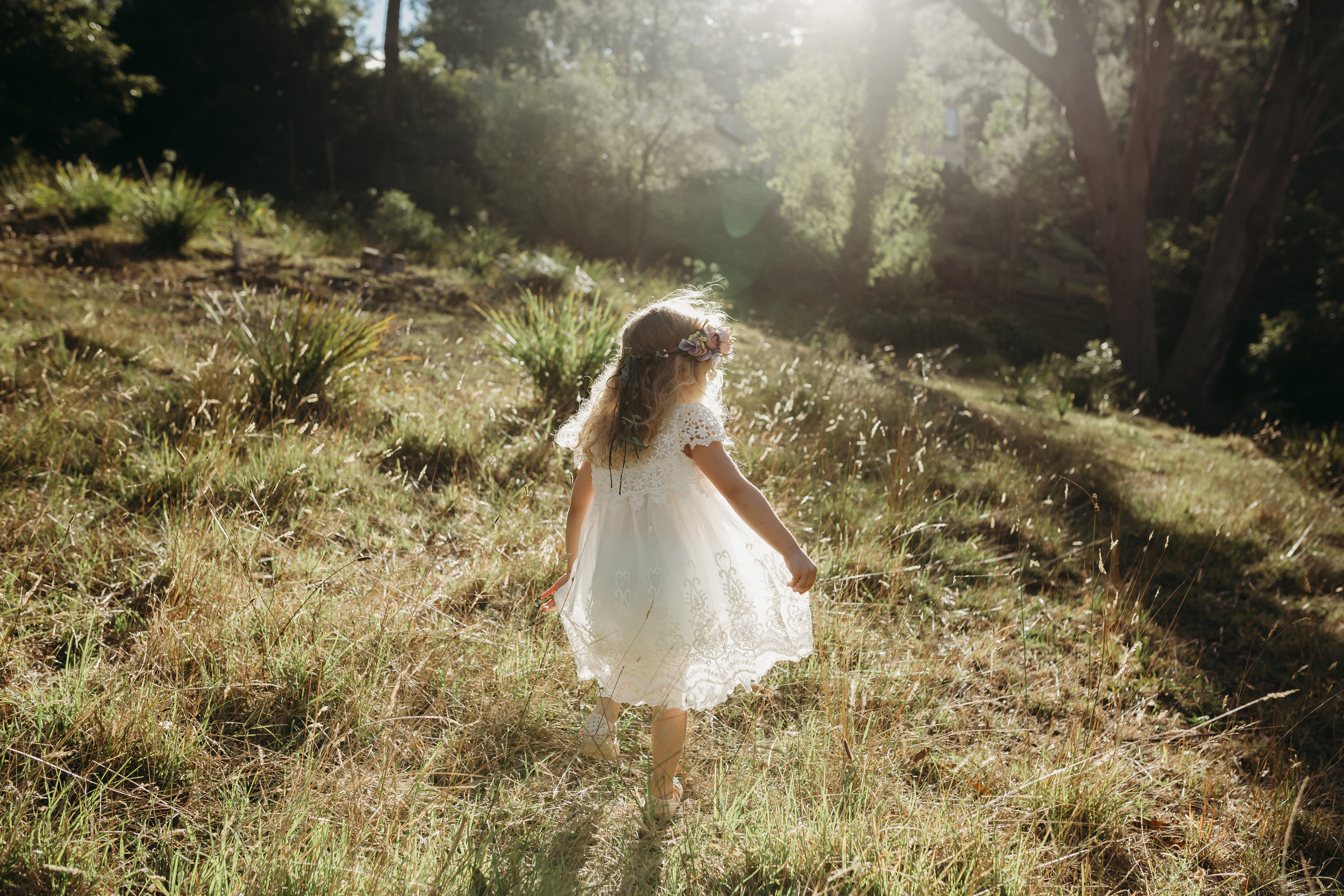 little girl twirling her dress in a field bathed in golden light