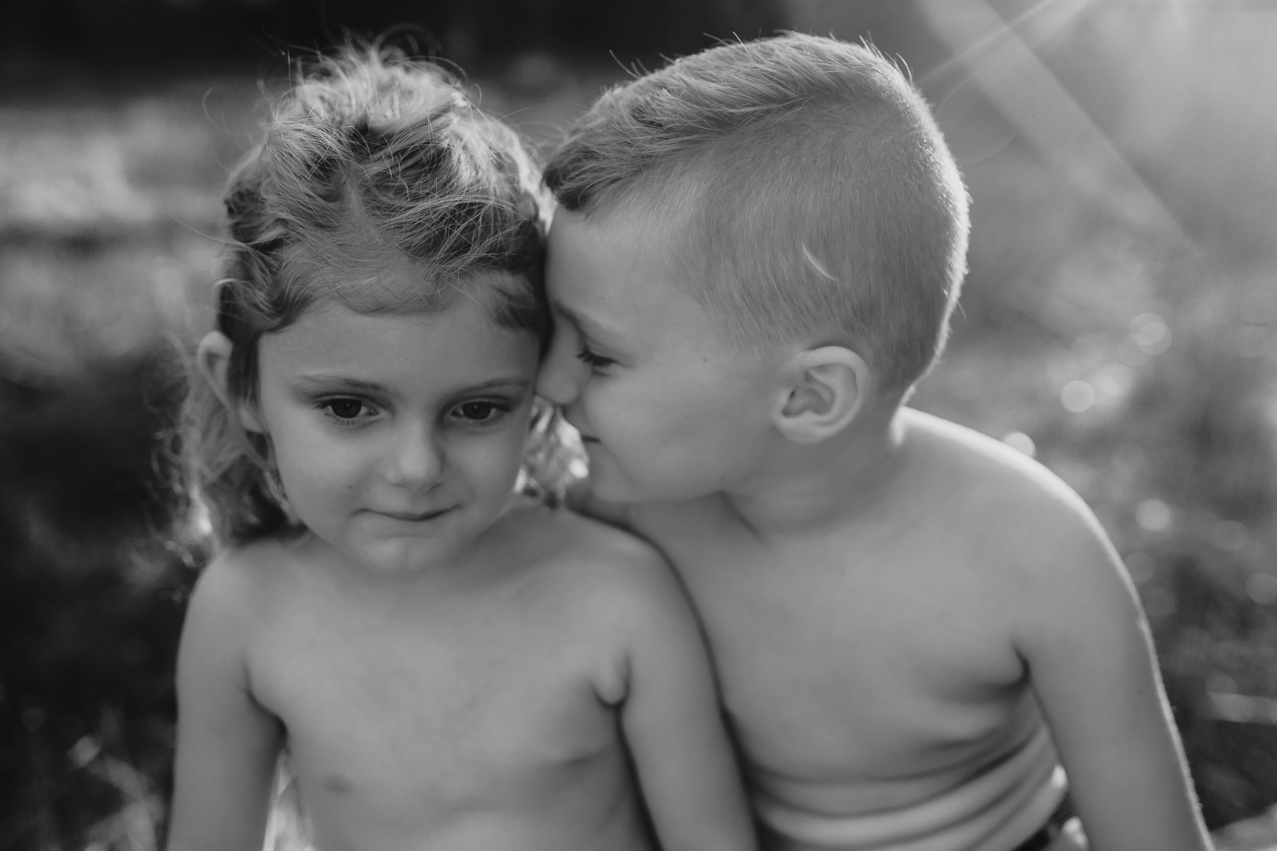 black and white photo of brother telling sister a secret