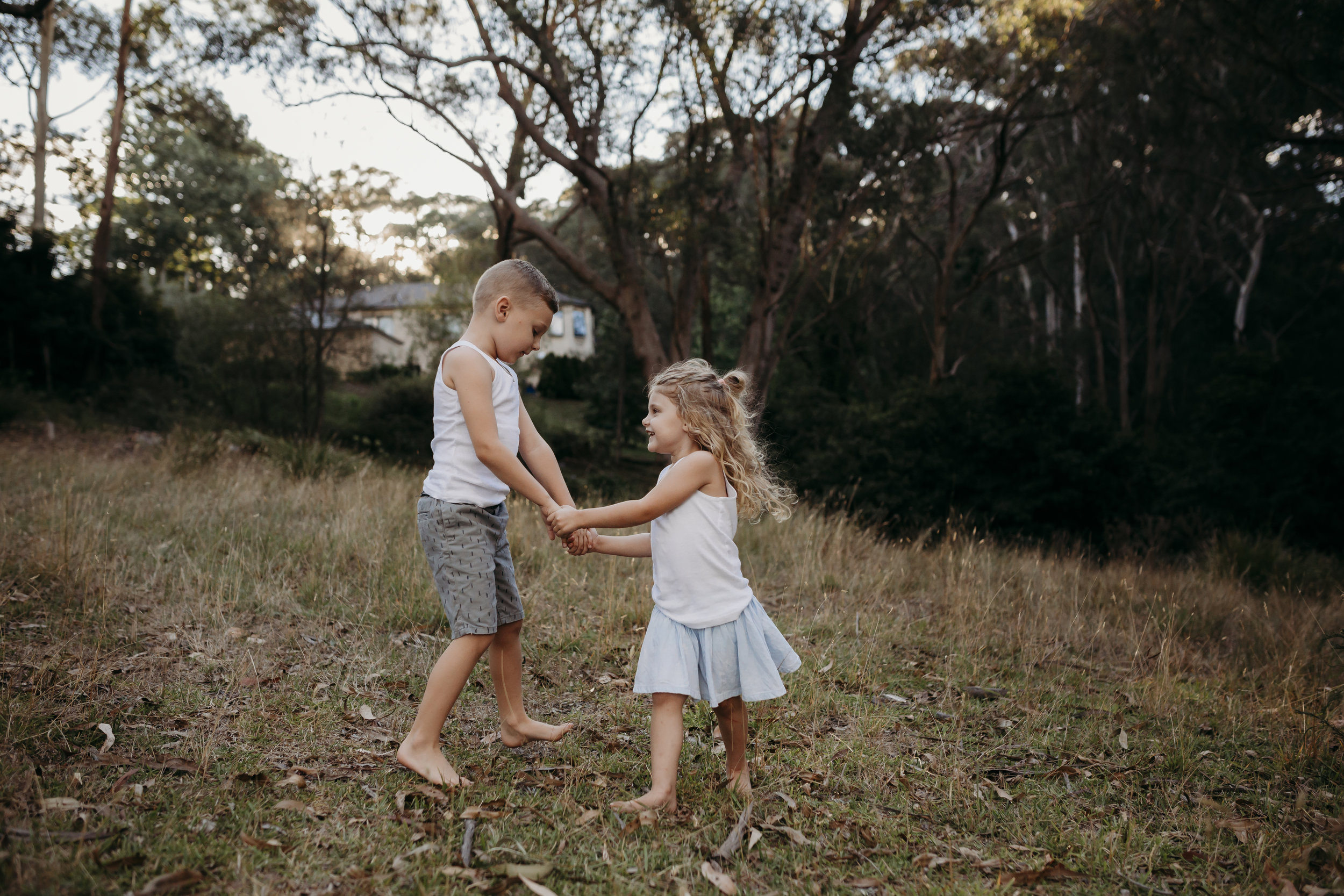 little boy and girl playing ring a ring a rosie