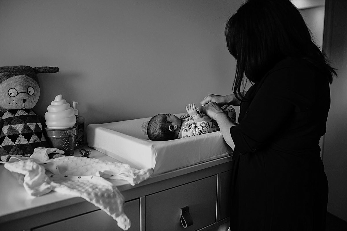 Black and White image of mother undressing newborn on change table
