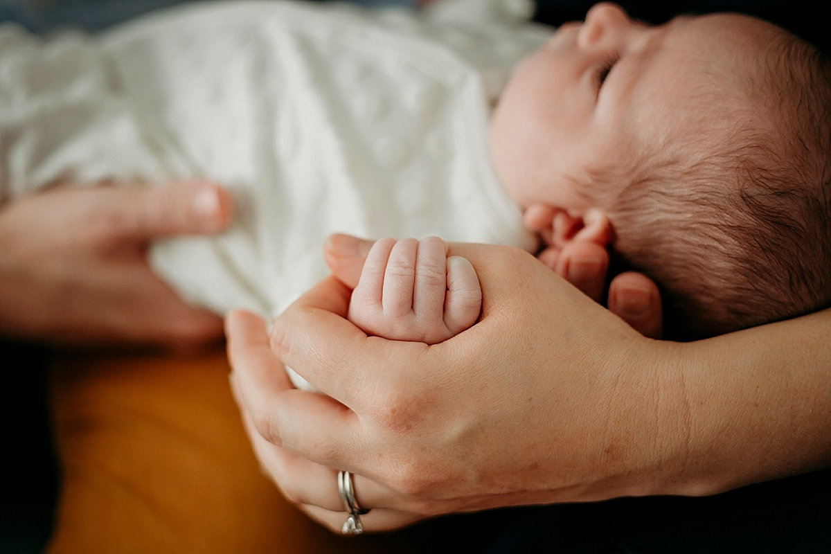 Baby girl holding thumb of mothers