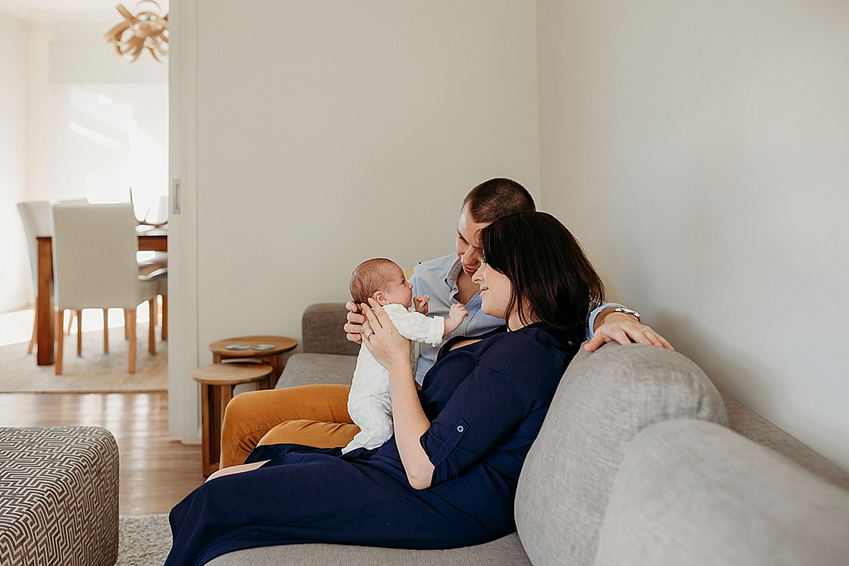 new family sitting on lounge playing with baby