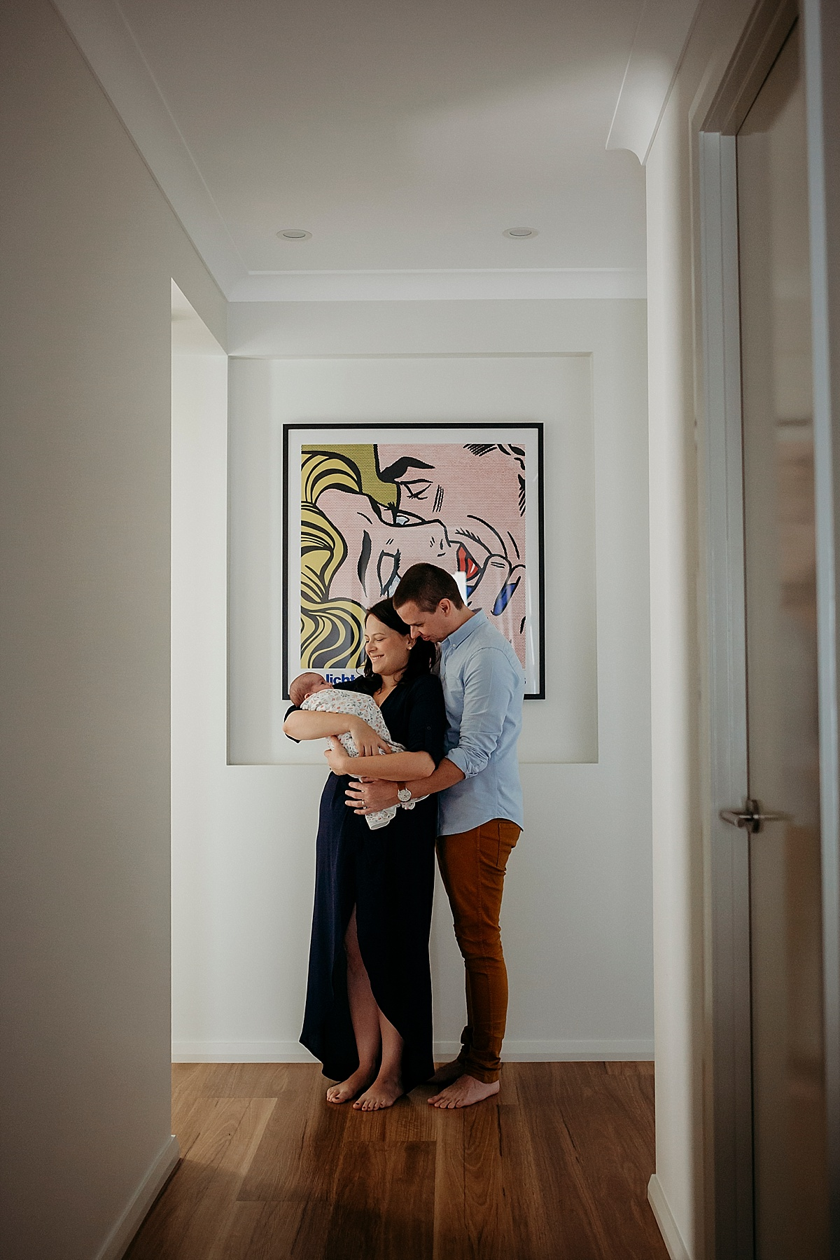 mum standing holding baby, with father hugging from behind, standing at end of hallway in front of artwork