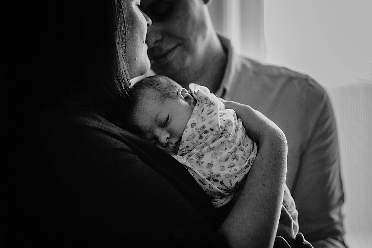 black and white image of baby laying on mums chest and dad leaning in