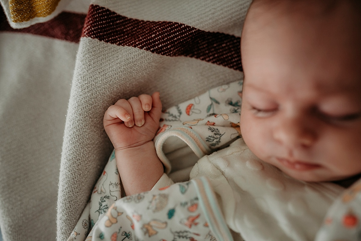 baby asleep on bed with hand up near head, fist clenched shut