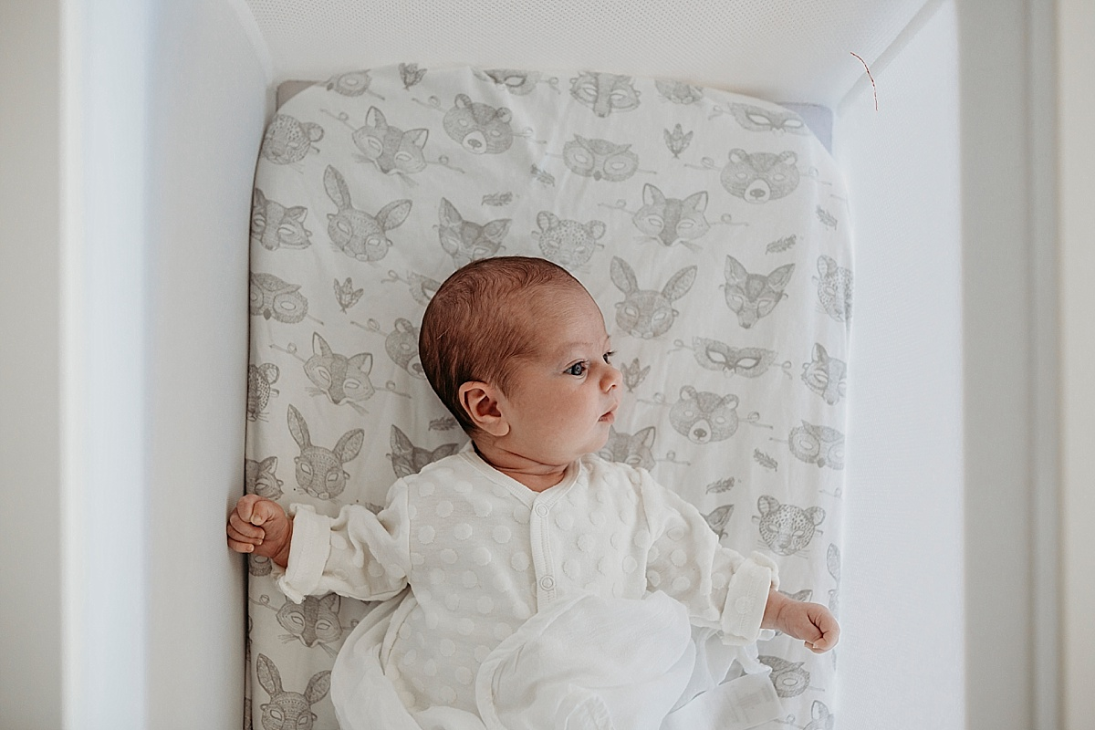 looking down on baby awake in bassinet