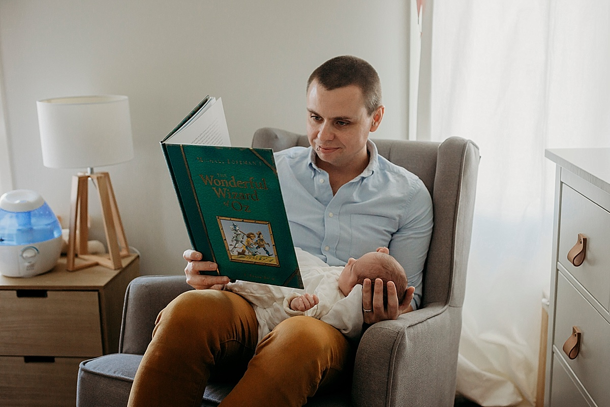 Father reading to his newborn born baby girl in chair