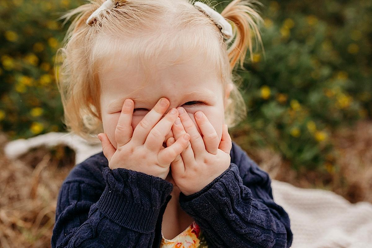 Baby girl playing peek a boo