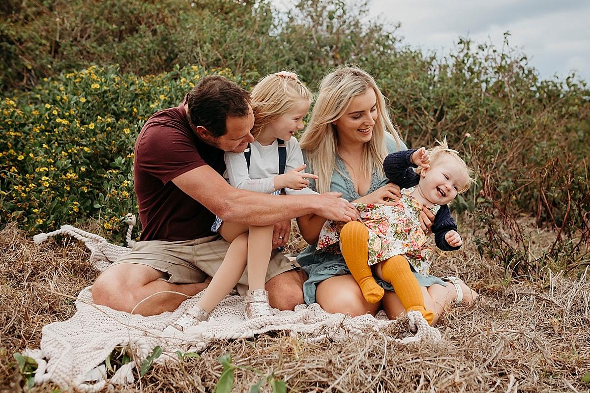 Family sitting, tickling daughter