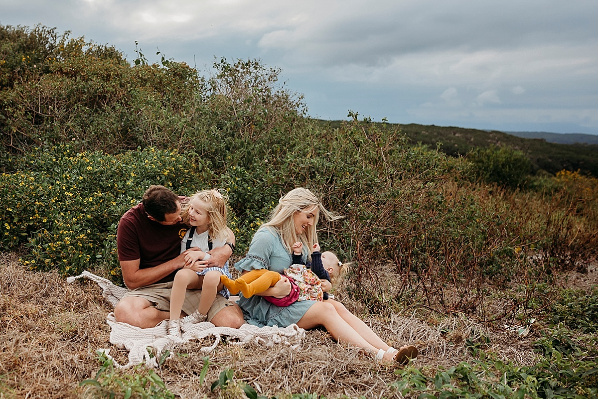Mum dad and two daughters playing while sitting down on picnic rug