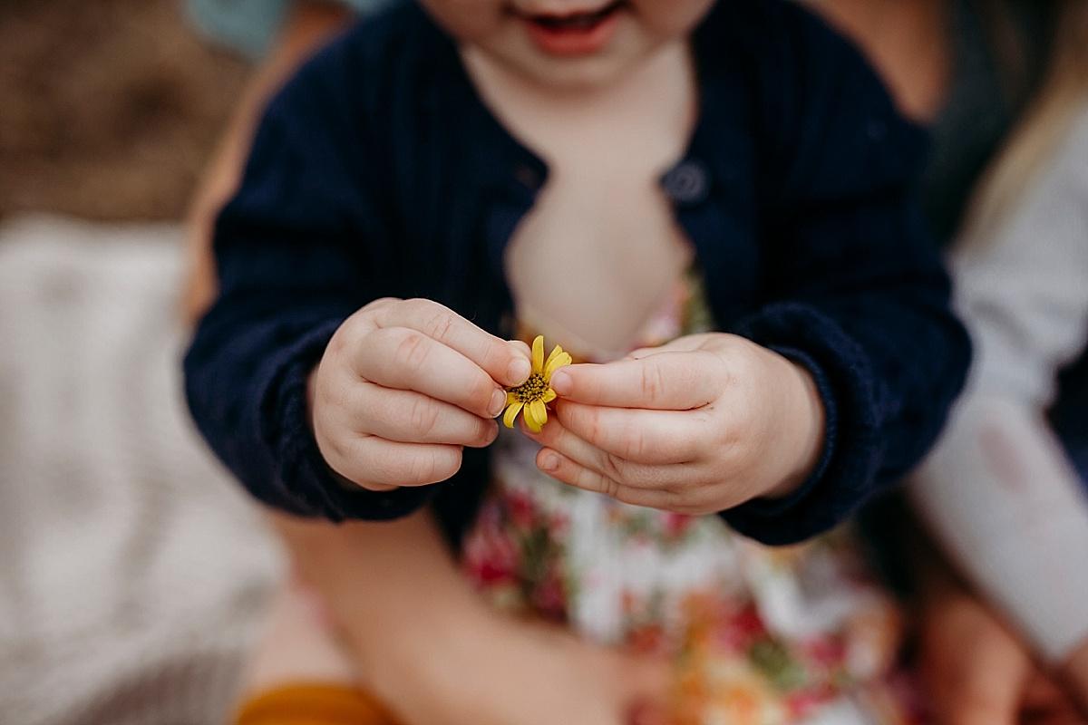 little yellow flower in baby girls fingers