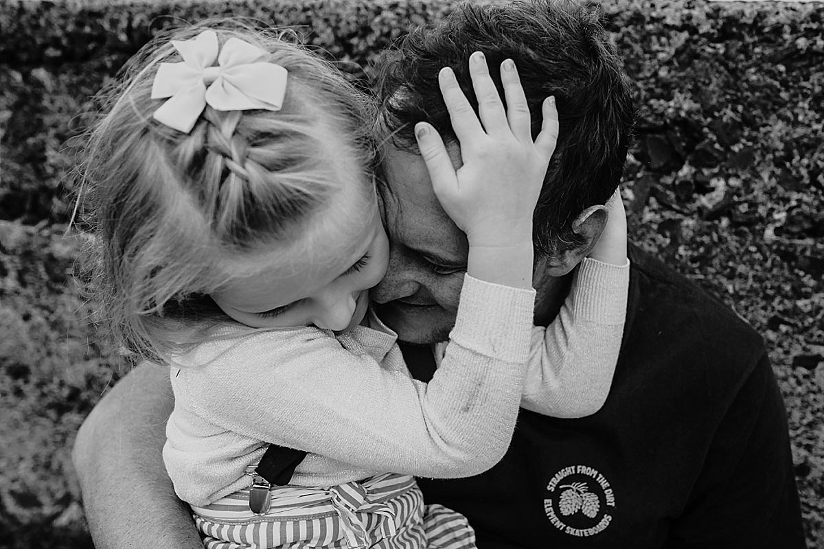 daughter cuddling dad head