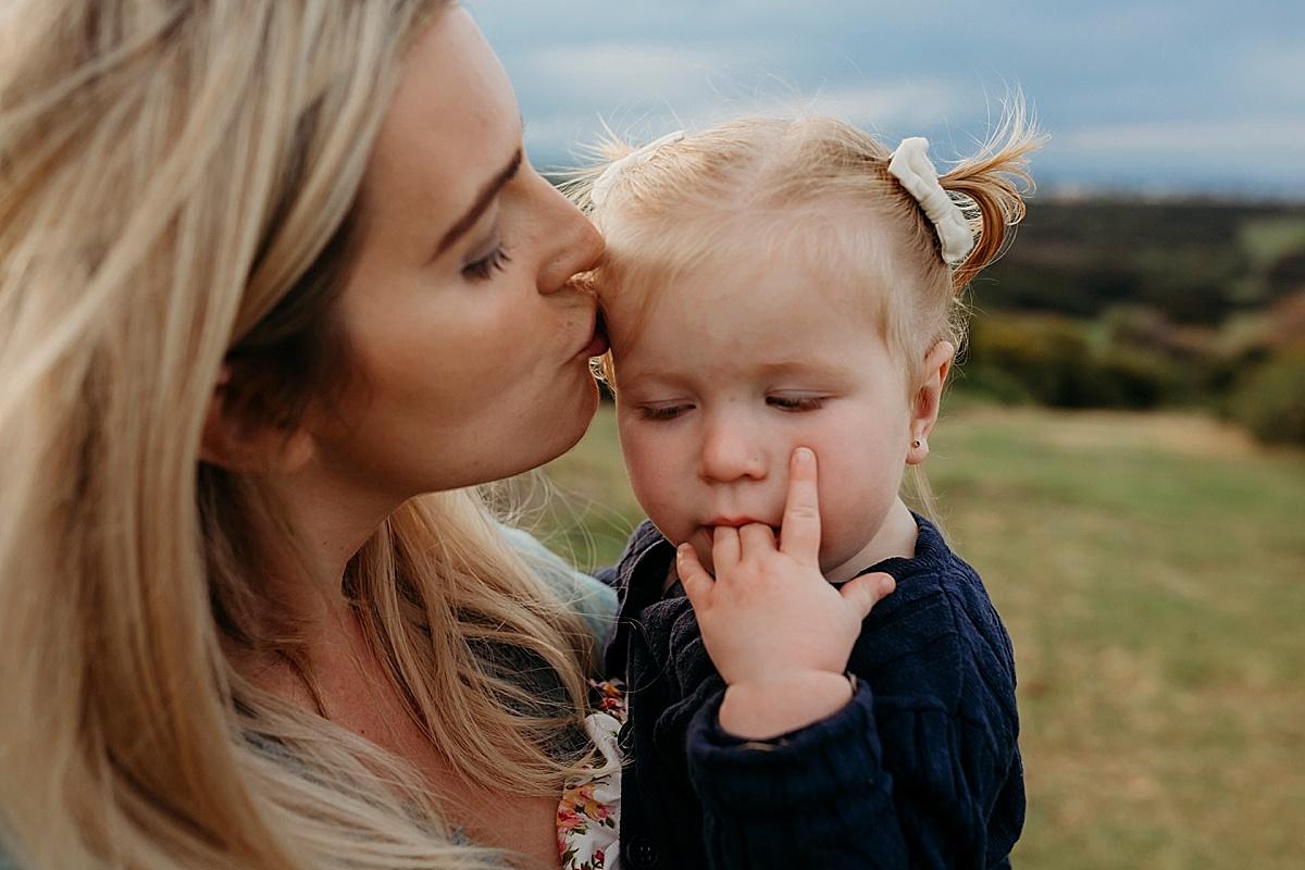 mum kissing little girl on head little girl sucking her fingers