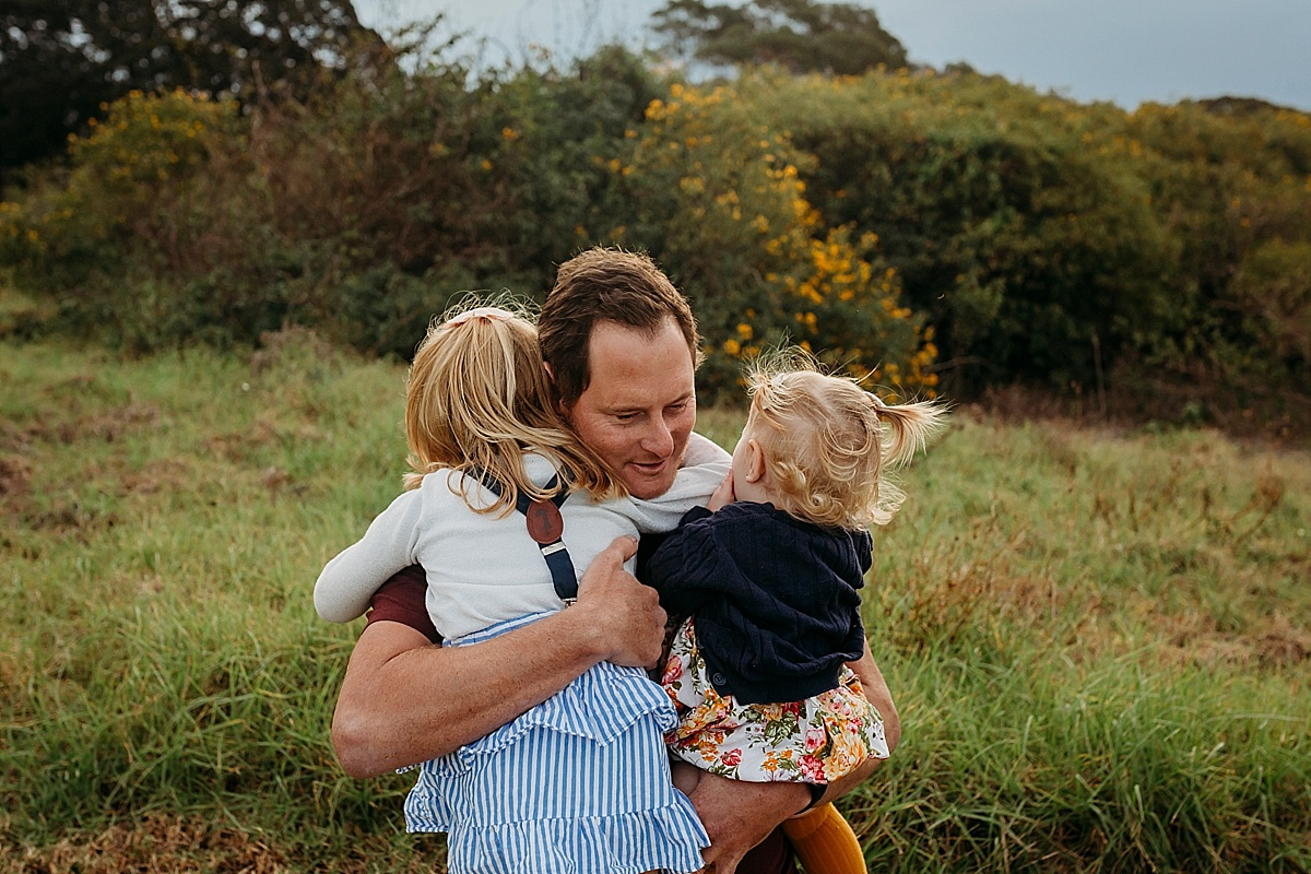 dad and his two daughters hugging him