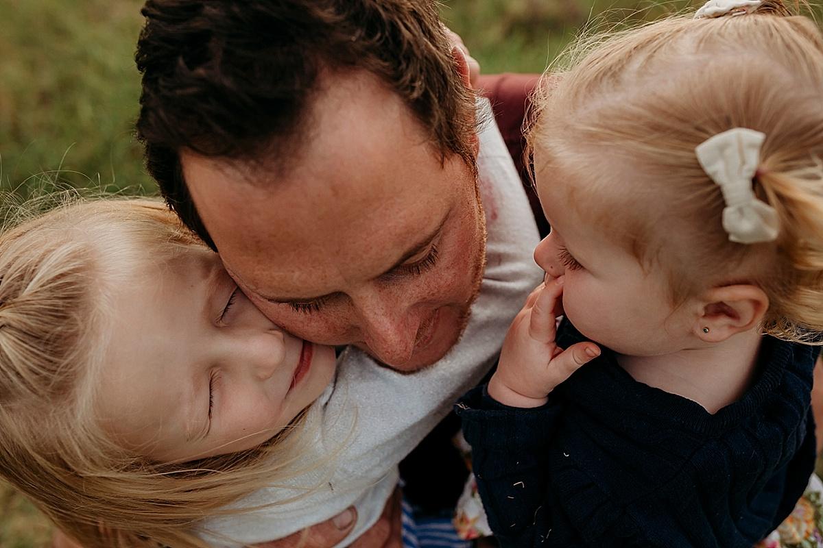 dad and little girls cuddling him