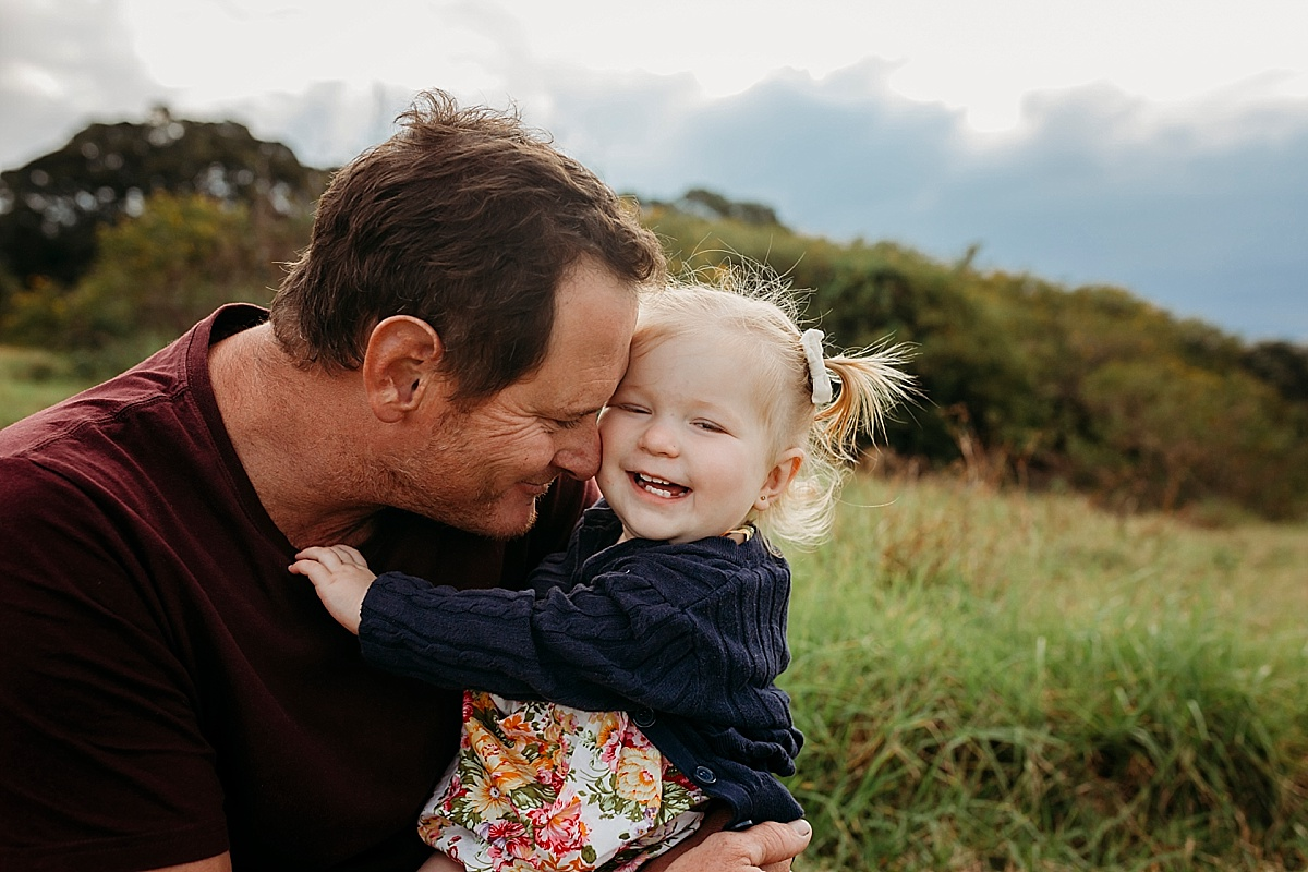 dad resting head against baby girl with baby girl looking at camera laughing