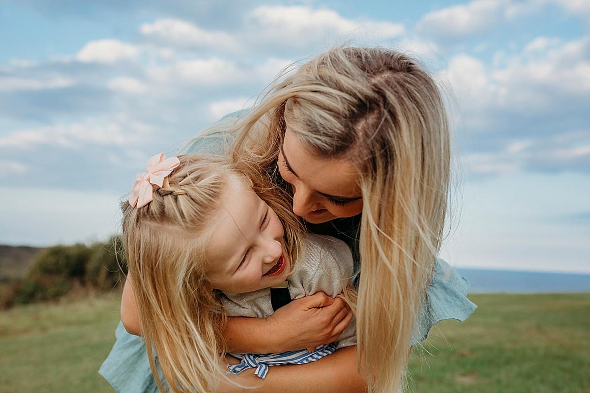 mum hugging daughter from behind