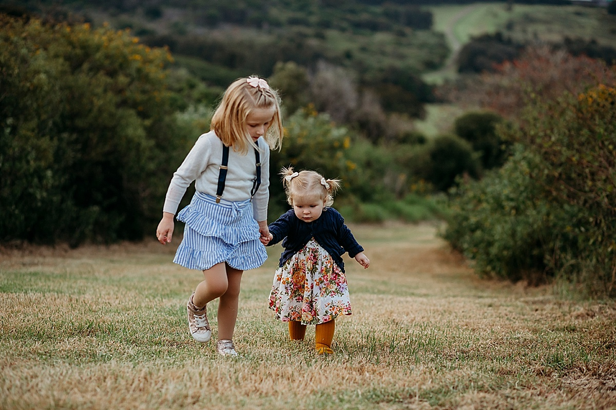 Sisters holding hands walking