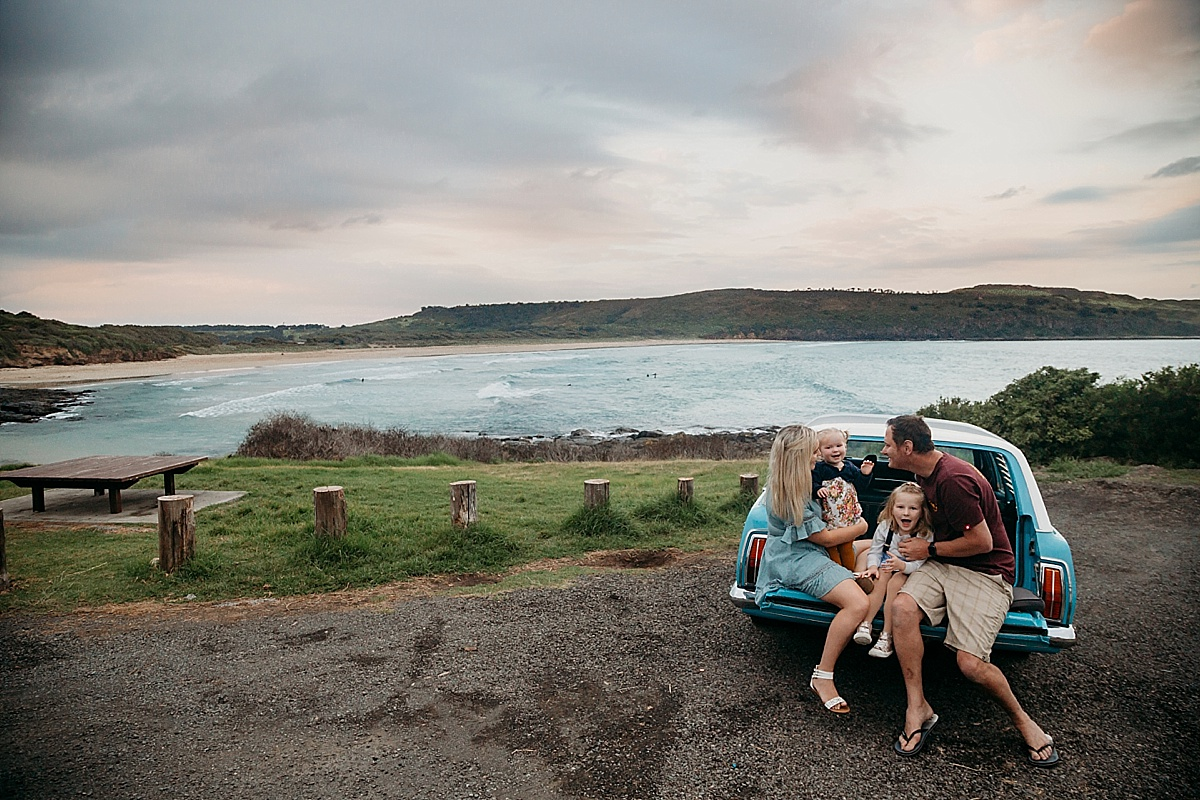 Family sitting on back of car, looking over the ocean