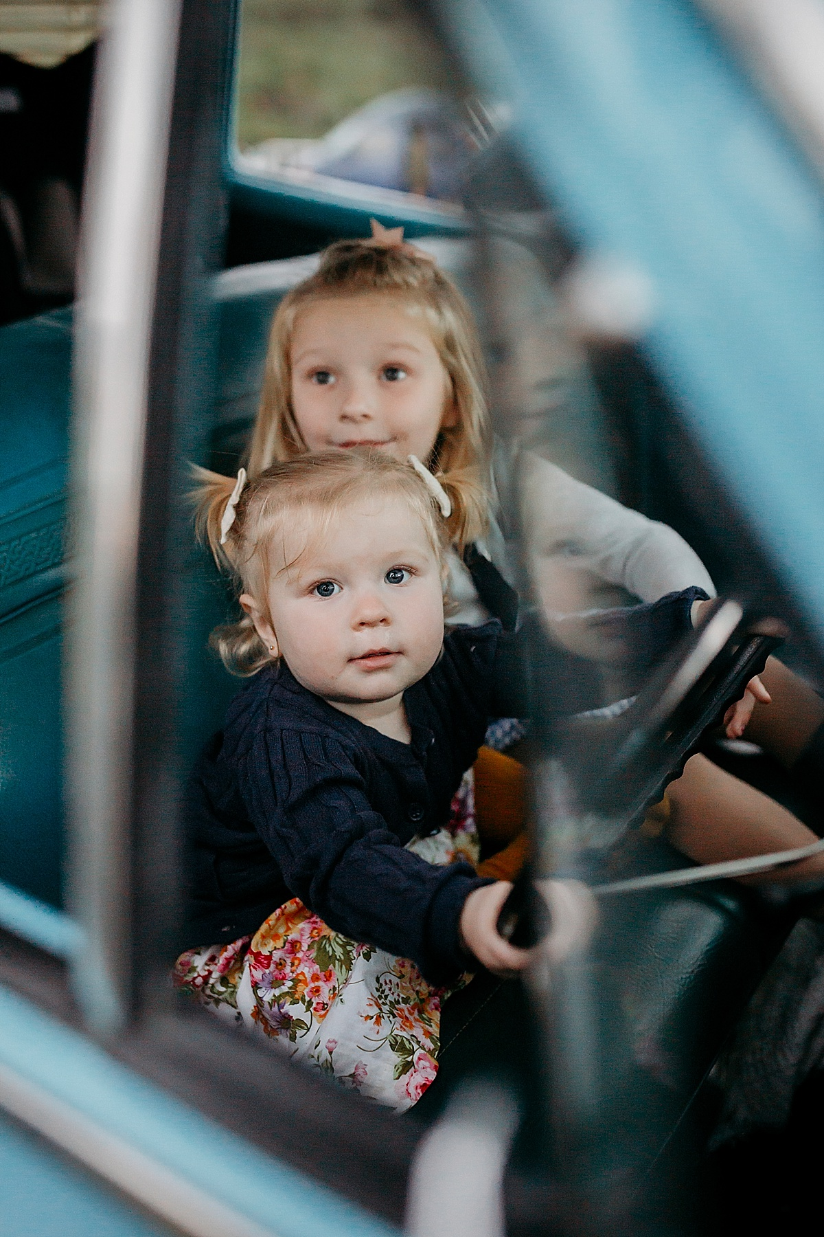 Two girls pretending to drive parents car