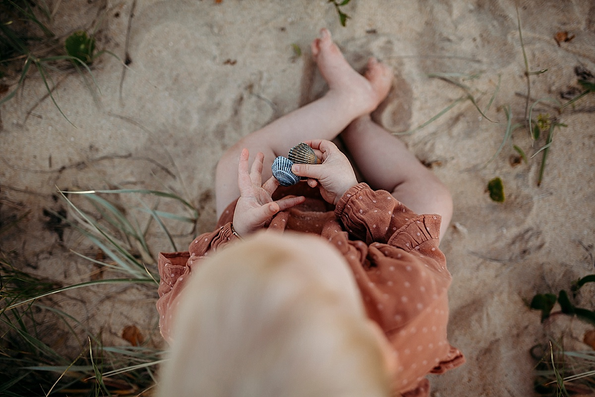 Little girl holding shells on beach