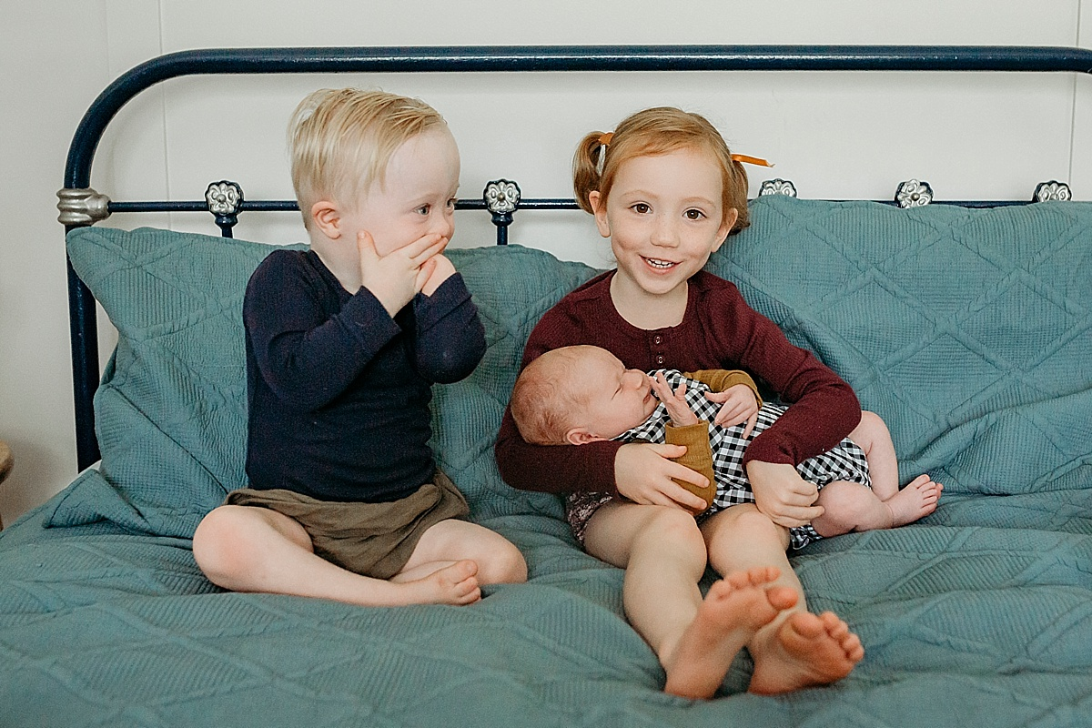 siblings on the bed, big sister holding newborn baby and little boy with hands over mouth in surprise