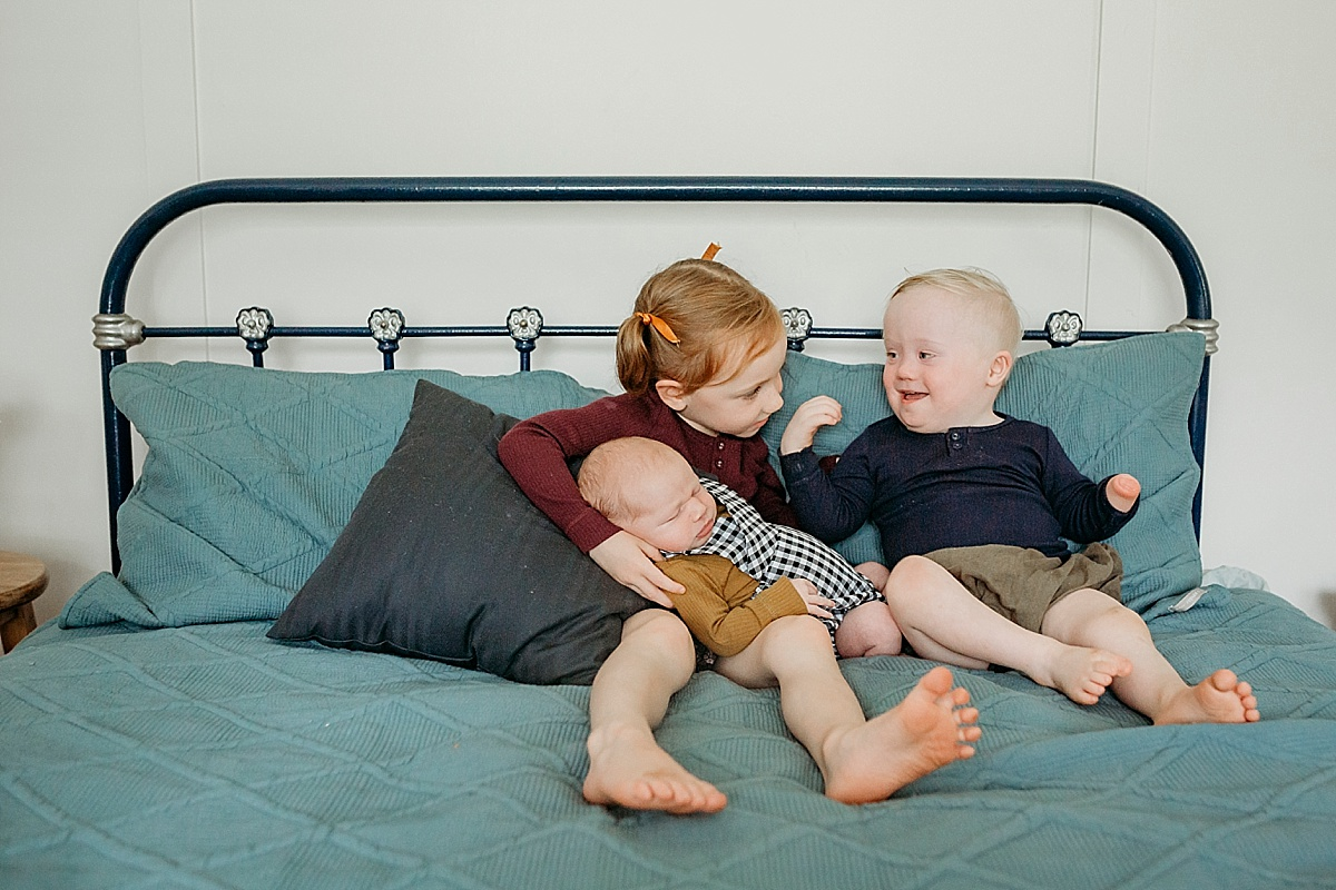 siblings on bed laughing