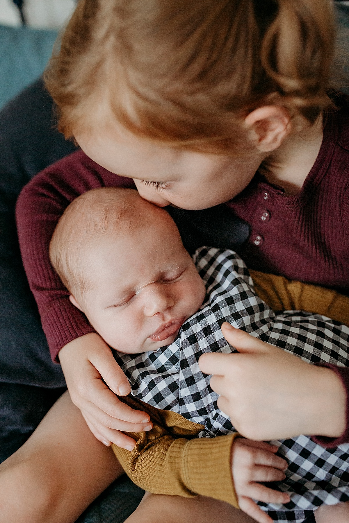 big sister holding newborn baby brother and kissing him on the head