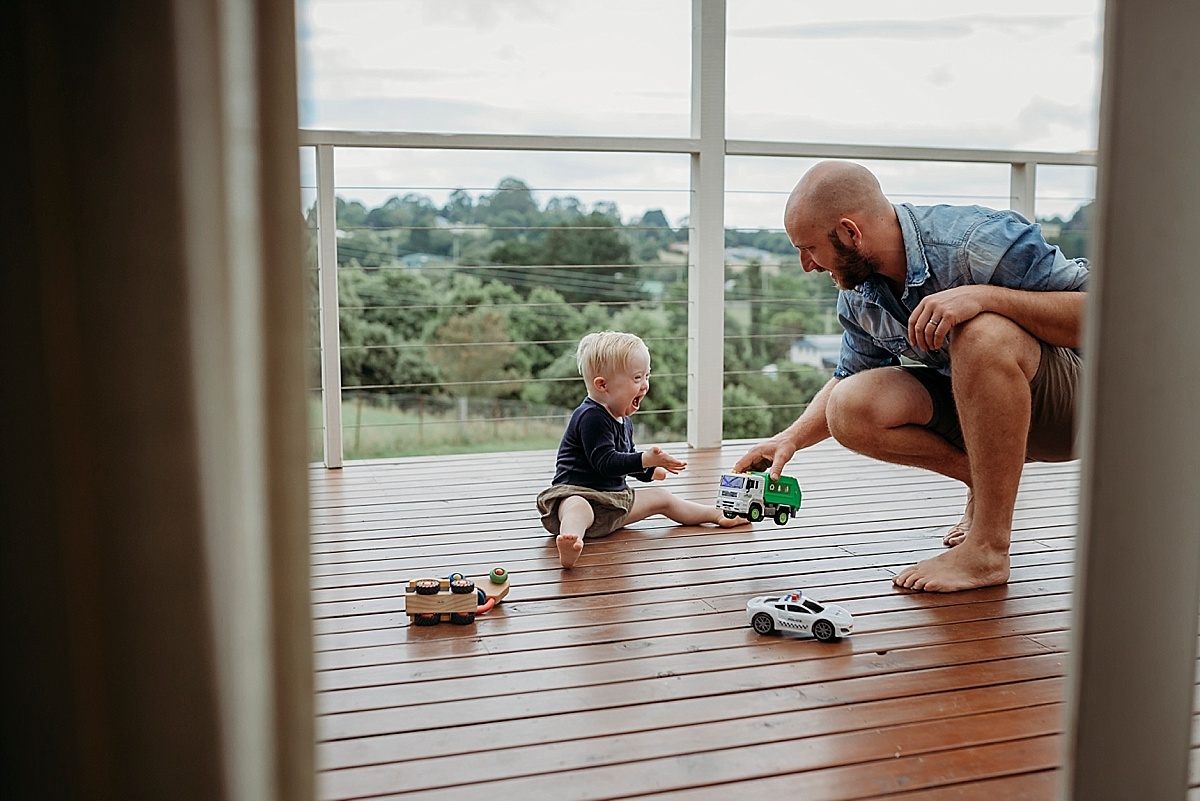 father and son playing on deck with cars and trucks