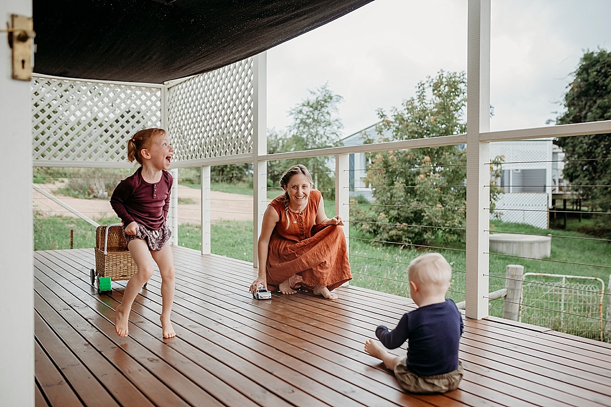 little girl dancing while mum and son play on deck with cars
