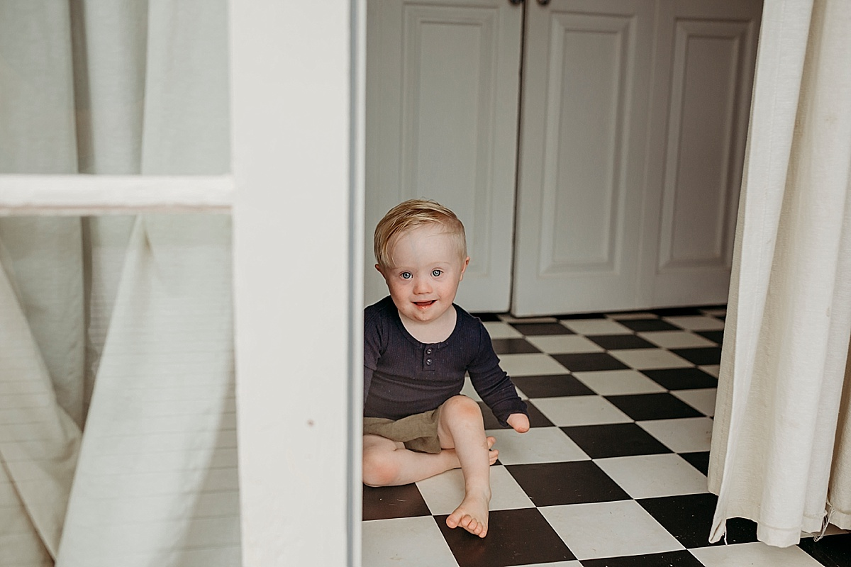 toddler with down syndrome and one had sitting on black and white floor just inside french doors
