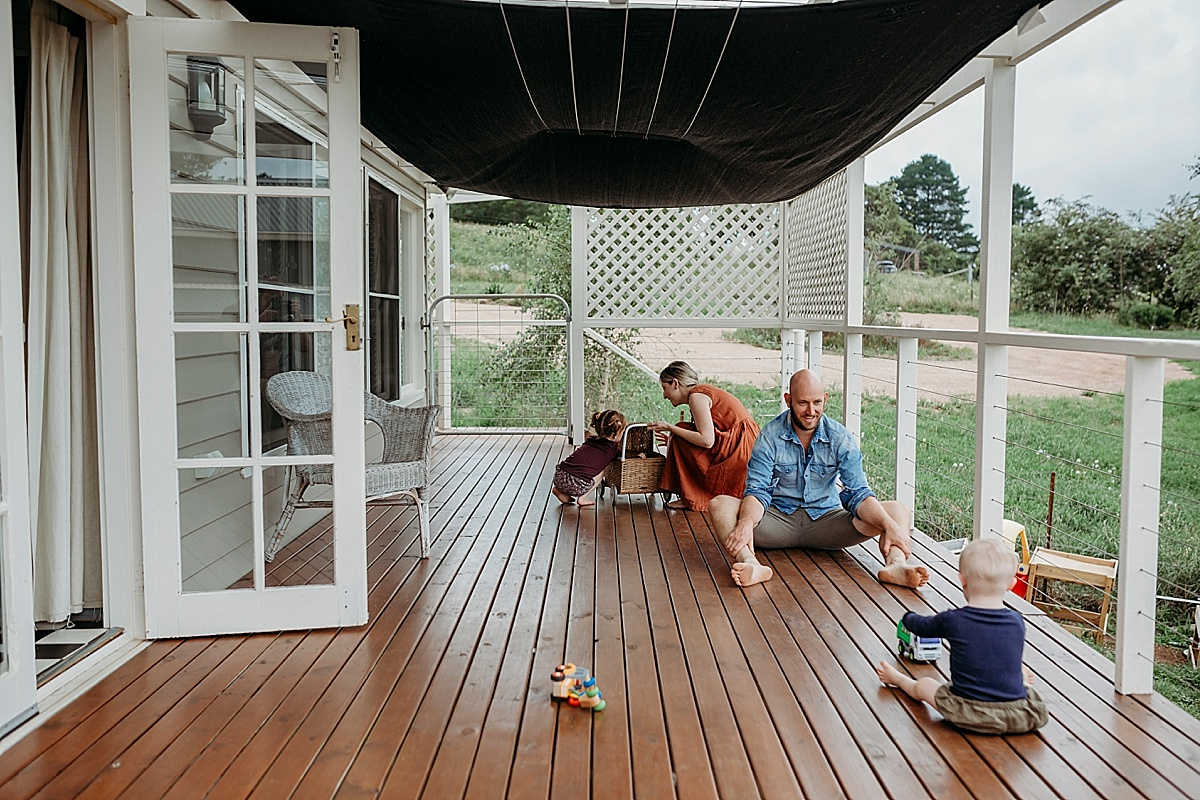 whole family playing on a back veranda in the country