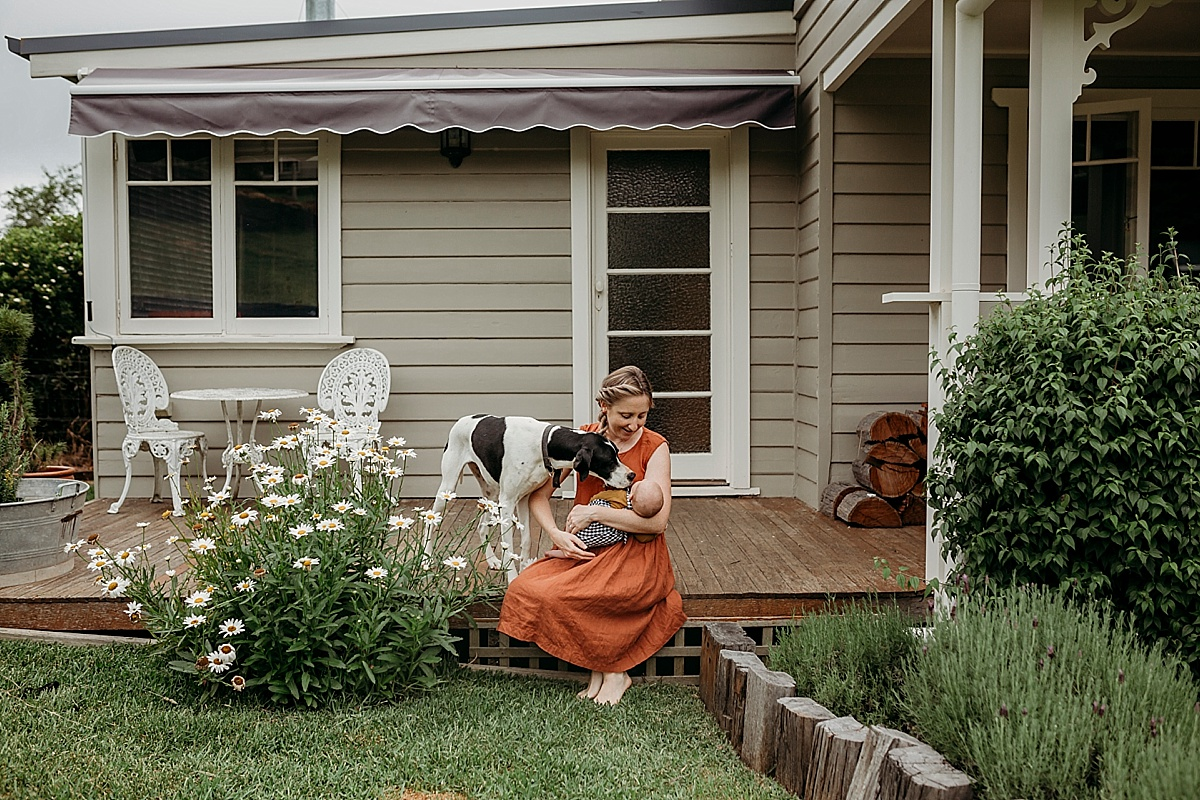mum and newborn baby sitting on front porch with their dog sniffing baby