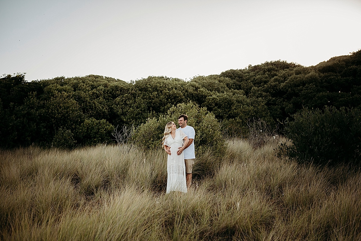 Man hugging pregnant wife while standing in long grass looking at each other