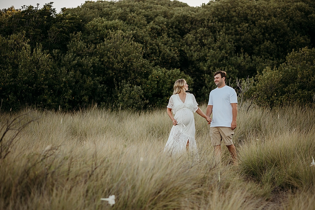 Pregnant wife leading husband by the had through long grass