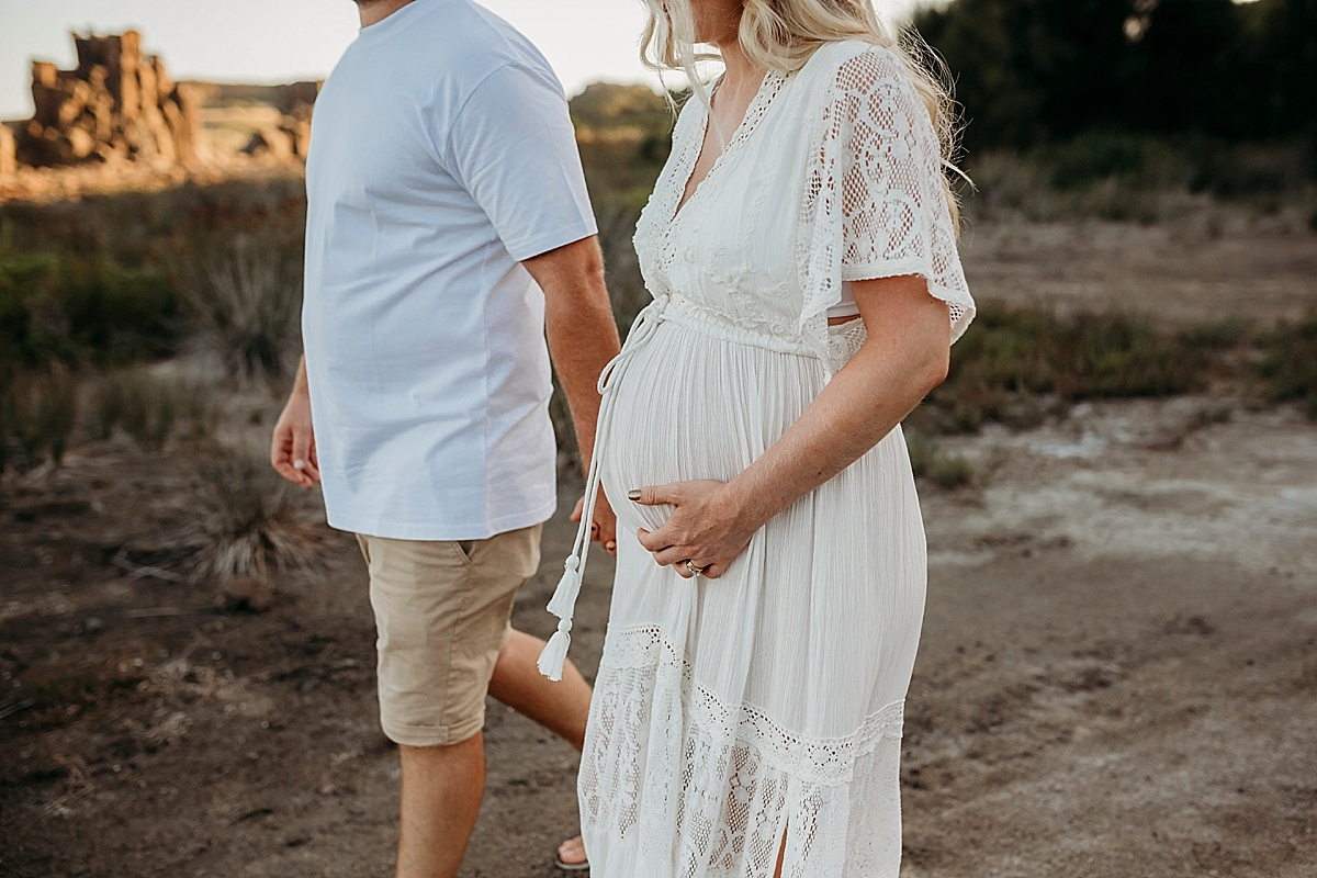 pregnant couple walking, focus on belly