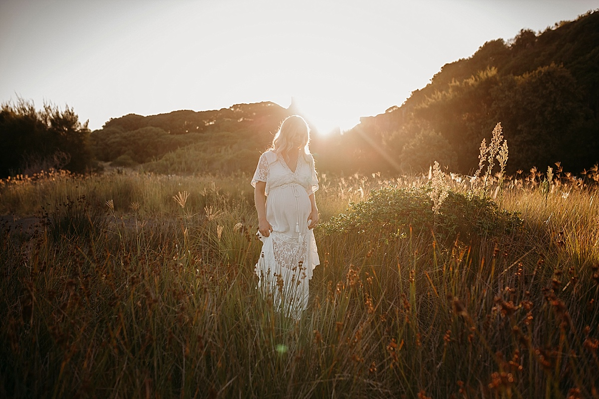 Pregnant mum walking through grass holding dress at sunset
