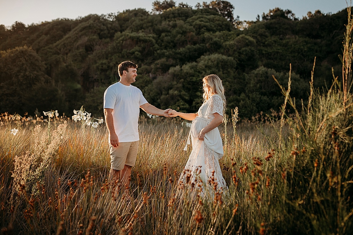 Pregnant mum dancing with husband in long reeds at sunset