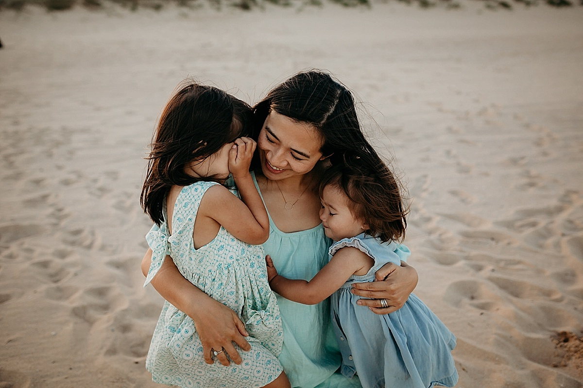 two little girls hugging their mum