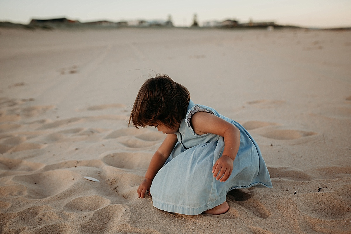 Little girl looking for shells in the sand on wollongong beach