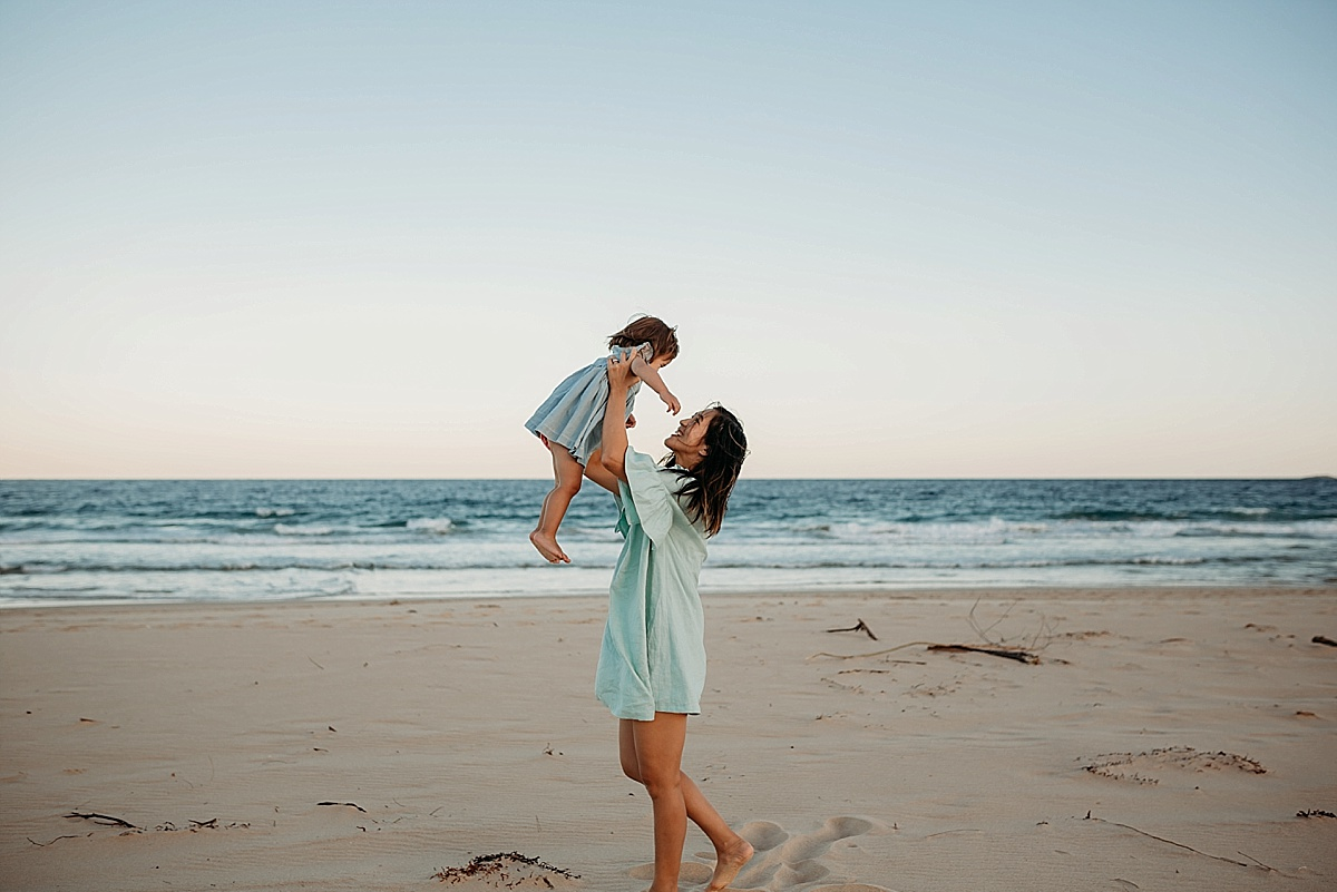 mum holding little girl up in the air at the beach at sunset