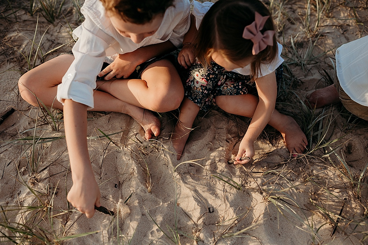 brother and sister drawing in sand together