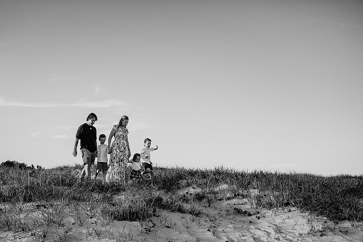 Family walking down sand dune at wollongong beach