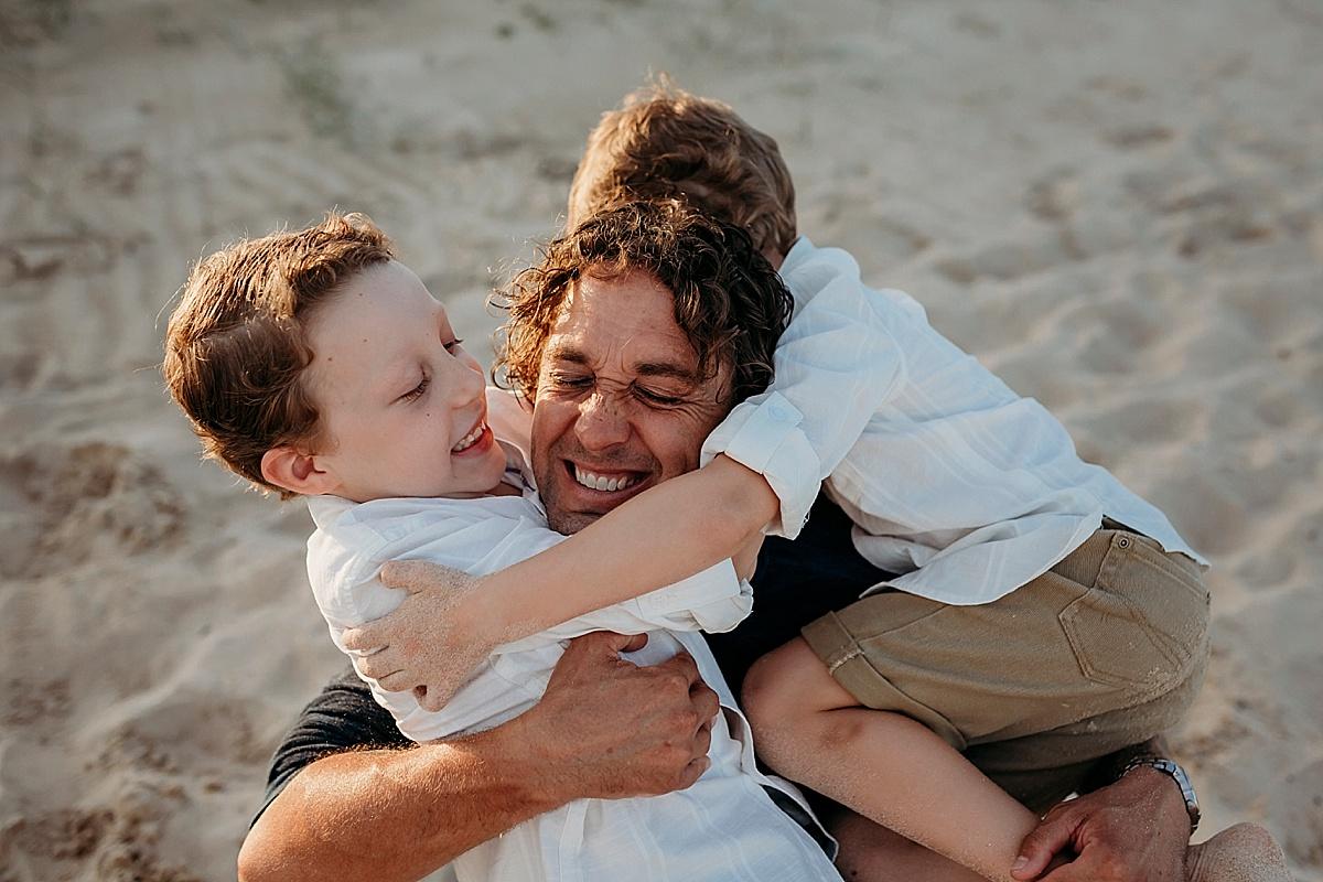 two sons tackling dad at beach