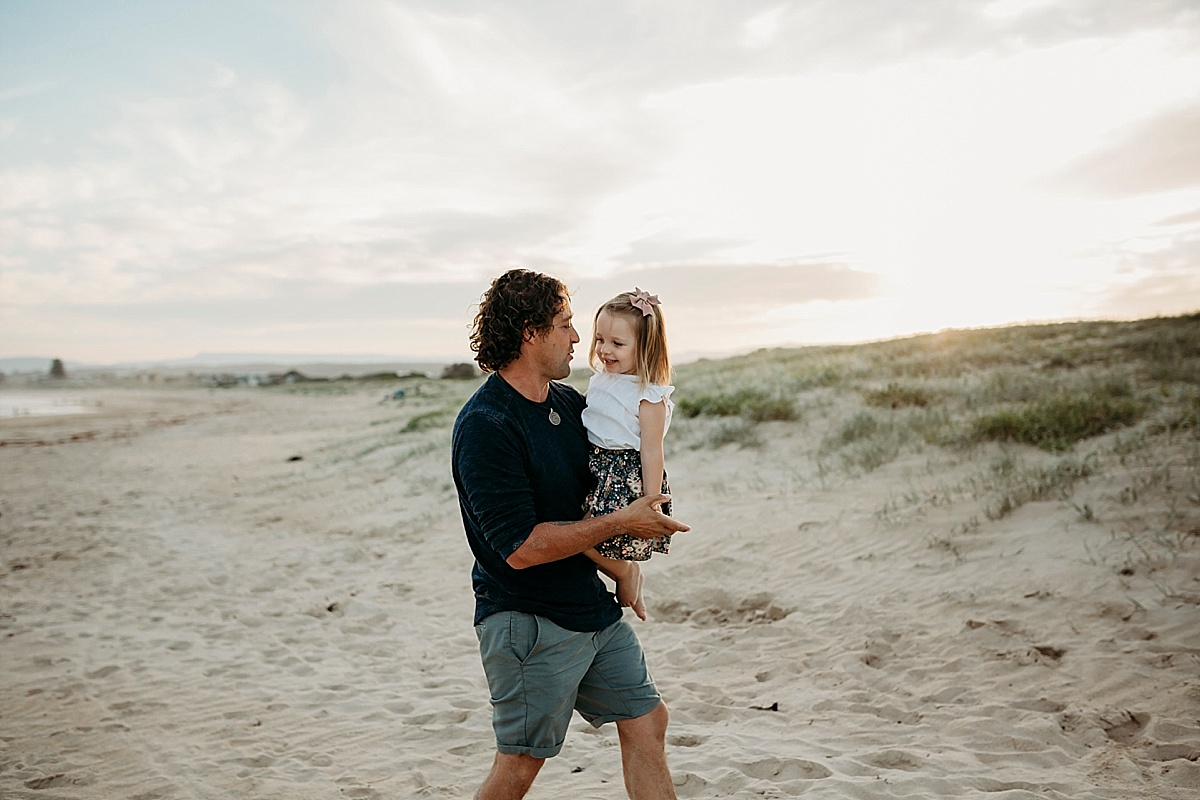 father and little girl dancing on beach at sunset