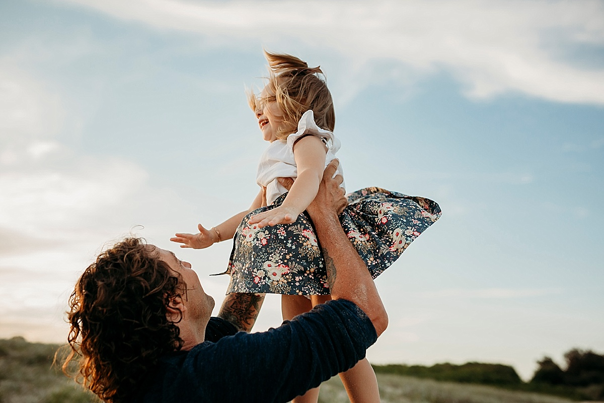 Little girl getting tossed into air by dad