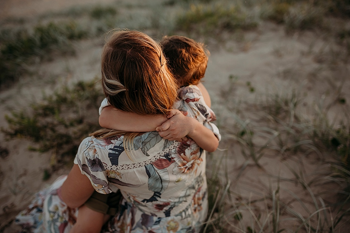 Boy wrapping arms around mums shoulders