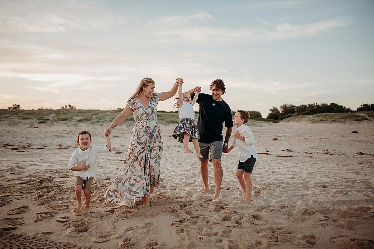 family holding hands walking along beach swinging little girls in air