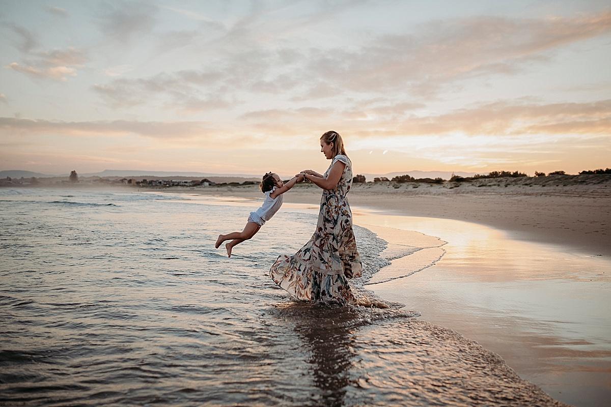 mum spinning daughter around in water
